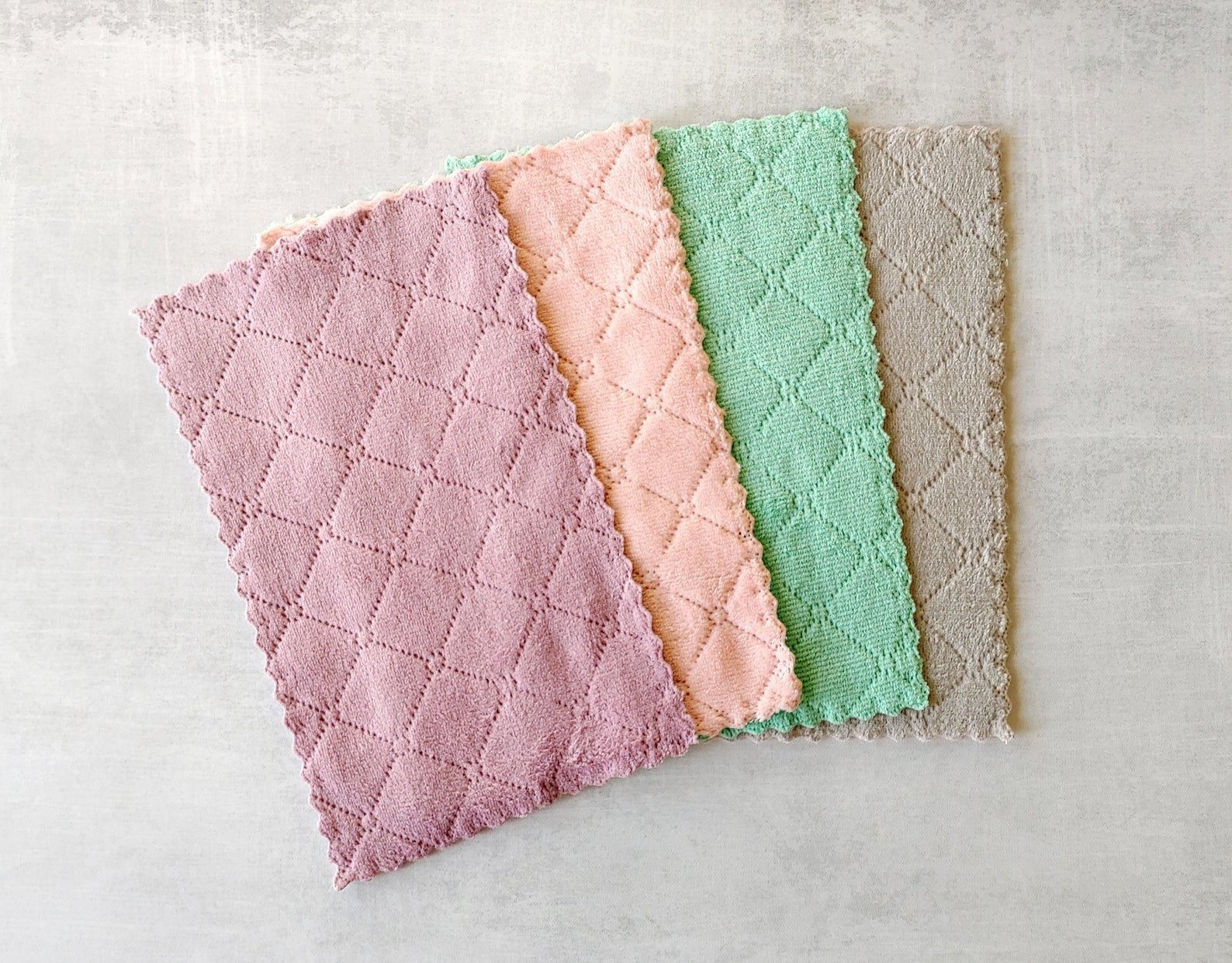 Four textured microfiber cloths in pink, light orange, green, and grey