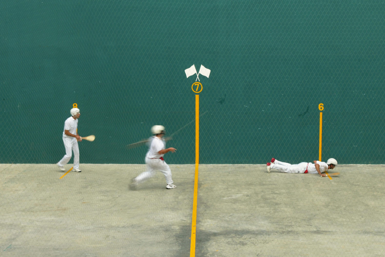 Three men playing Pelota