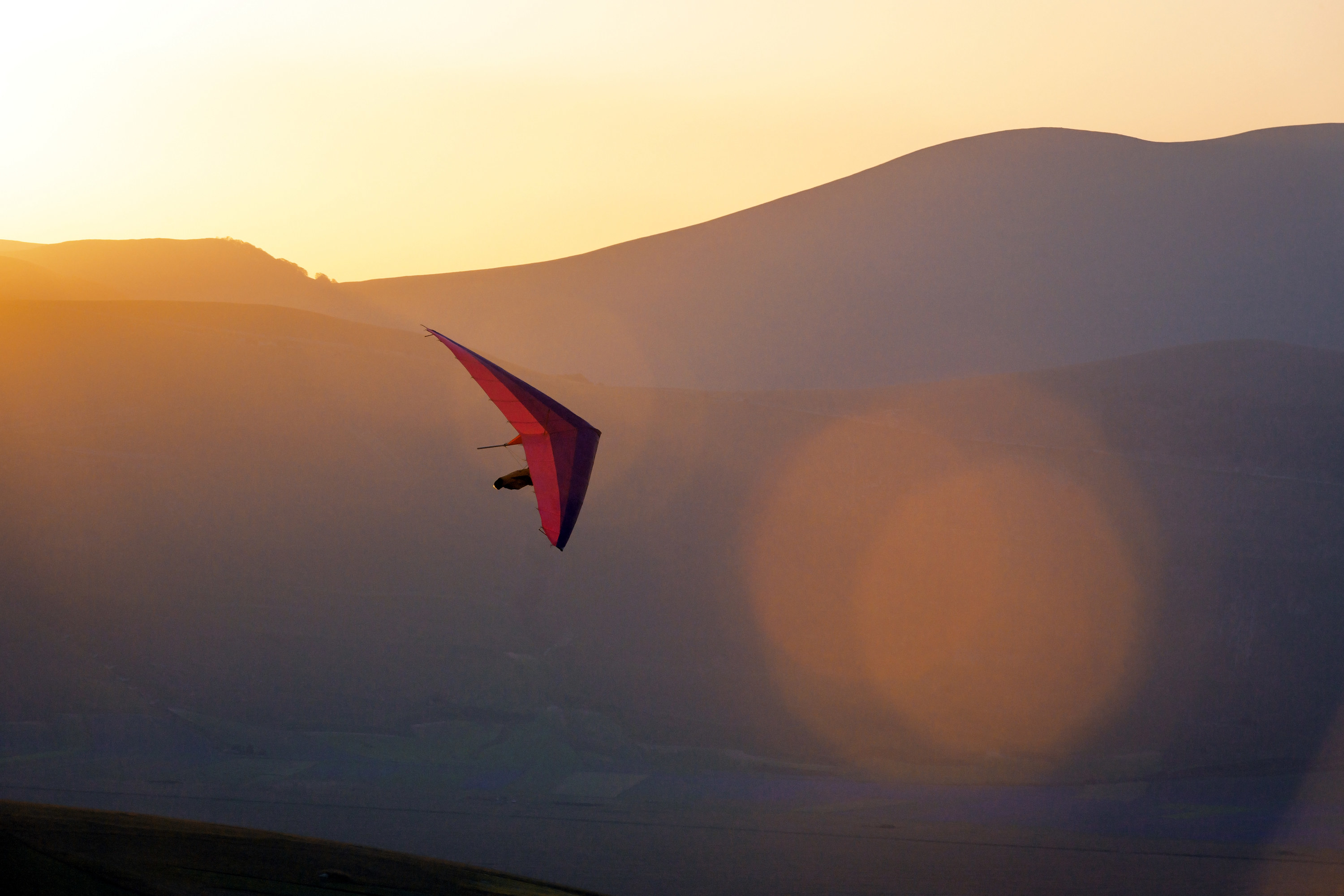 Man gliding during the sunset