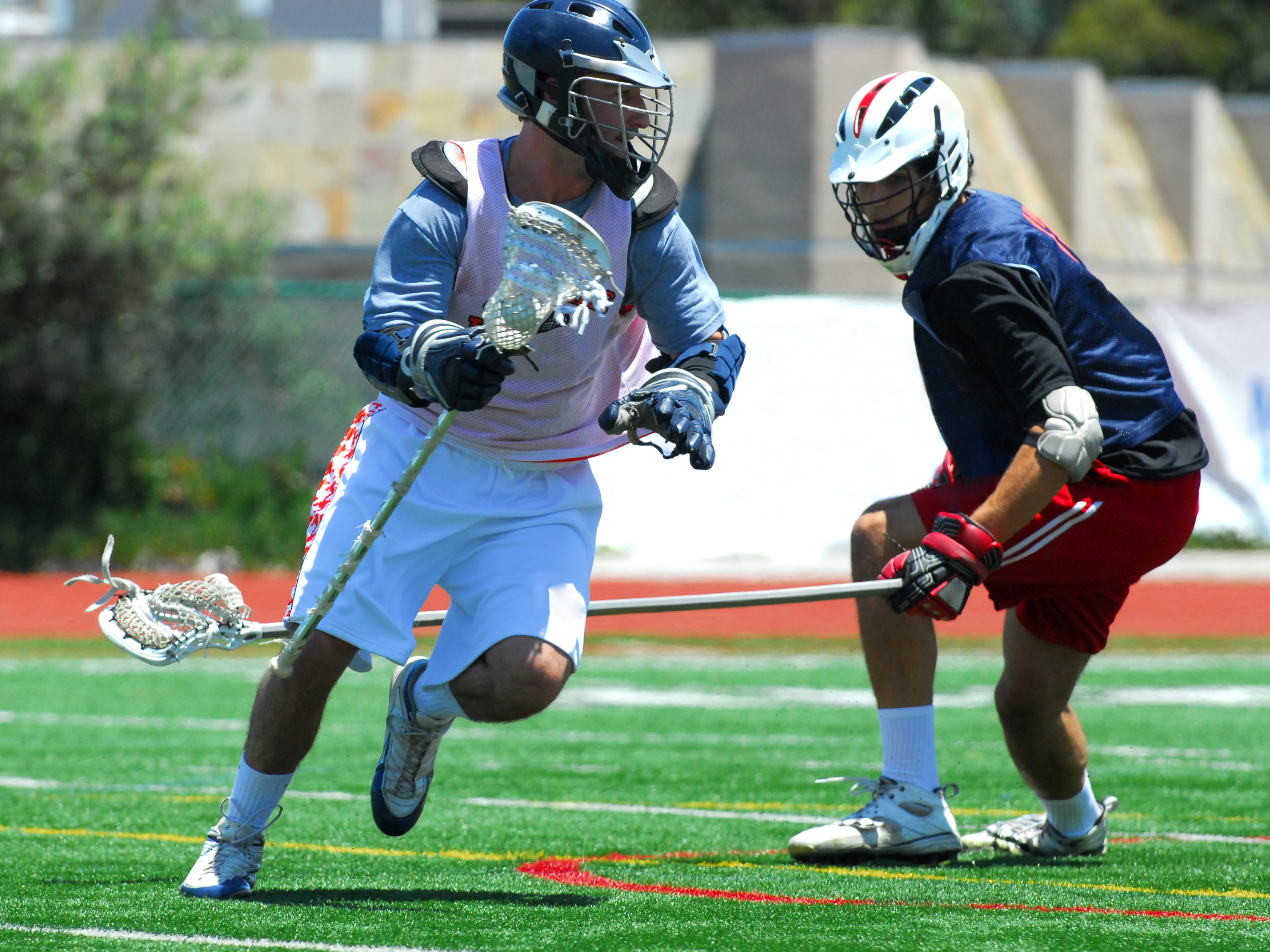 One lacrosse player chasing another