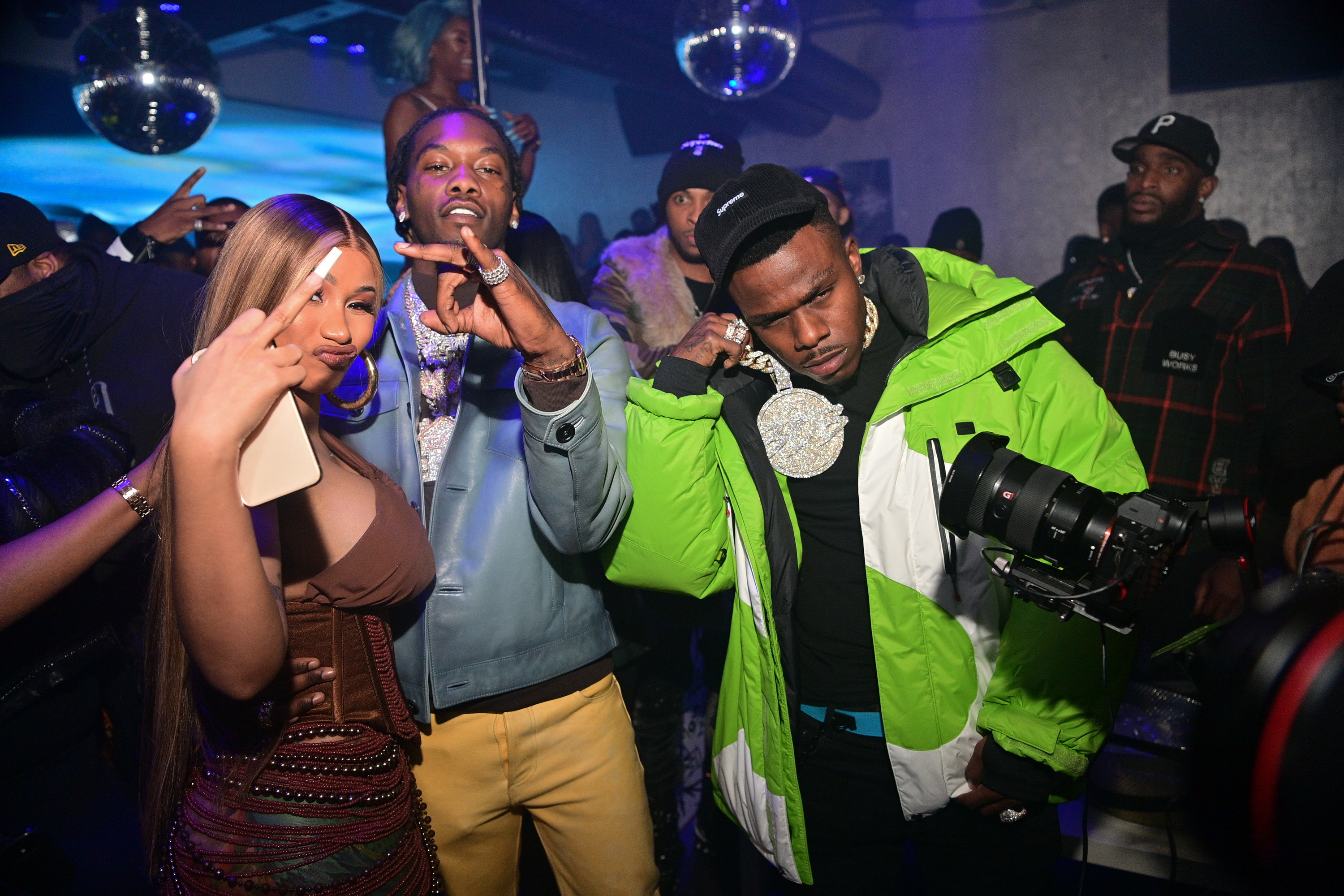 Cardi, Offset and DaBaby posing for photos at an event