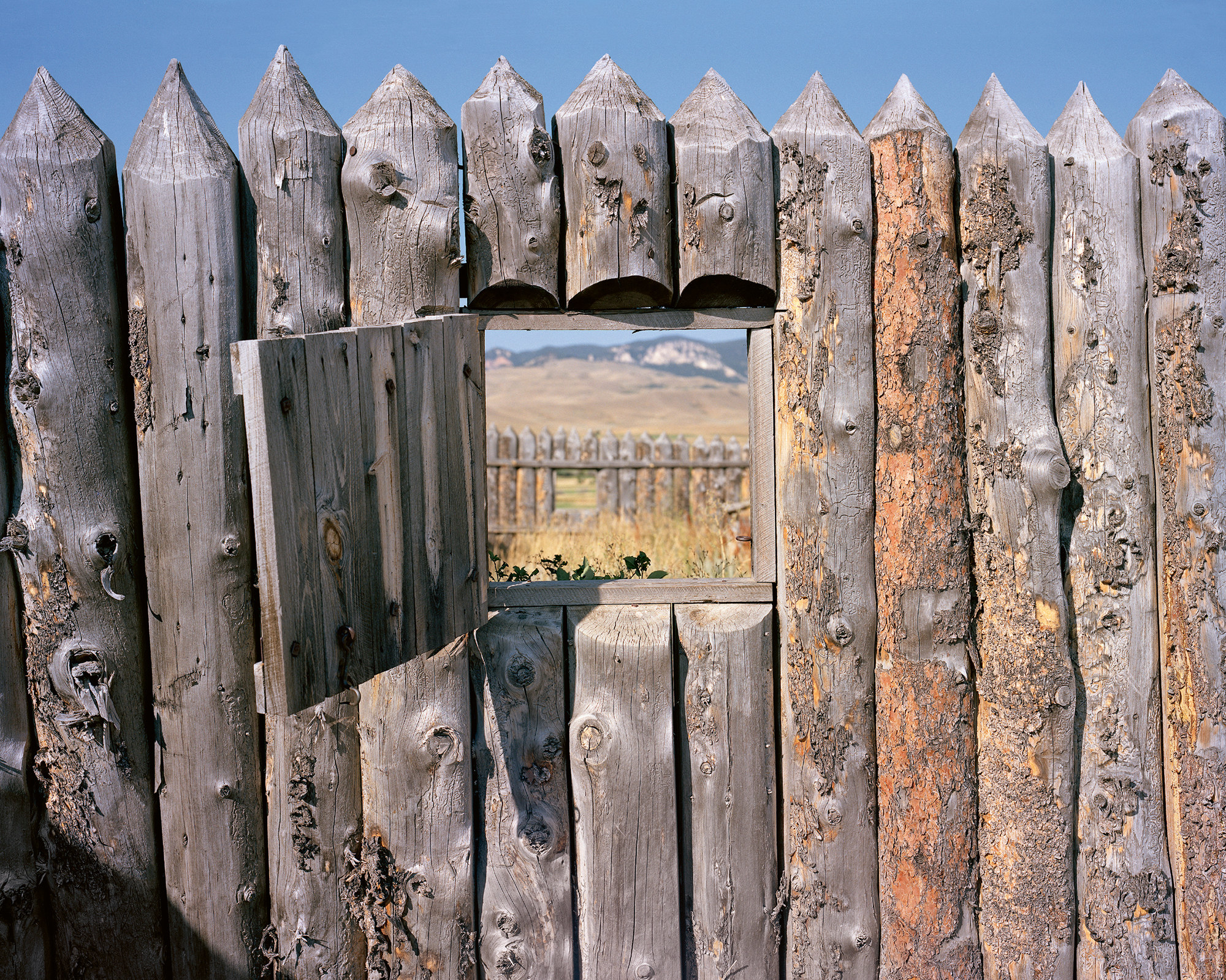 A window cut into walls made out of wood opens out into another row of wood walls and arid grassland
