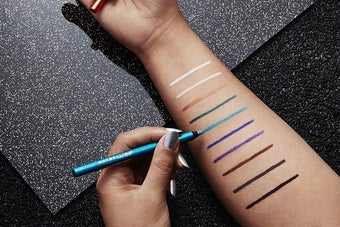 An arm holding an assortment of the Maybelline eyeliner, plus swatches of 10 different shades, including metallic colors and neutrals like black and brown