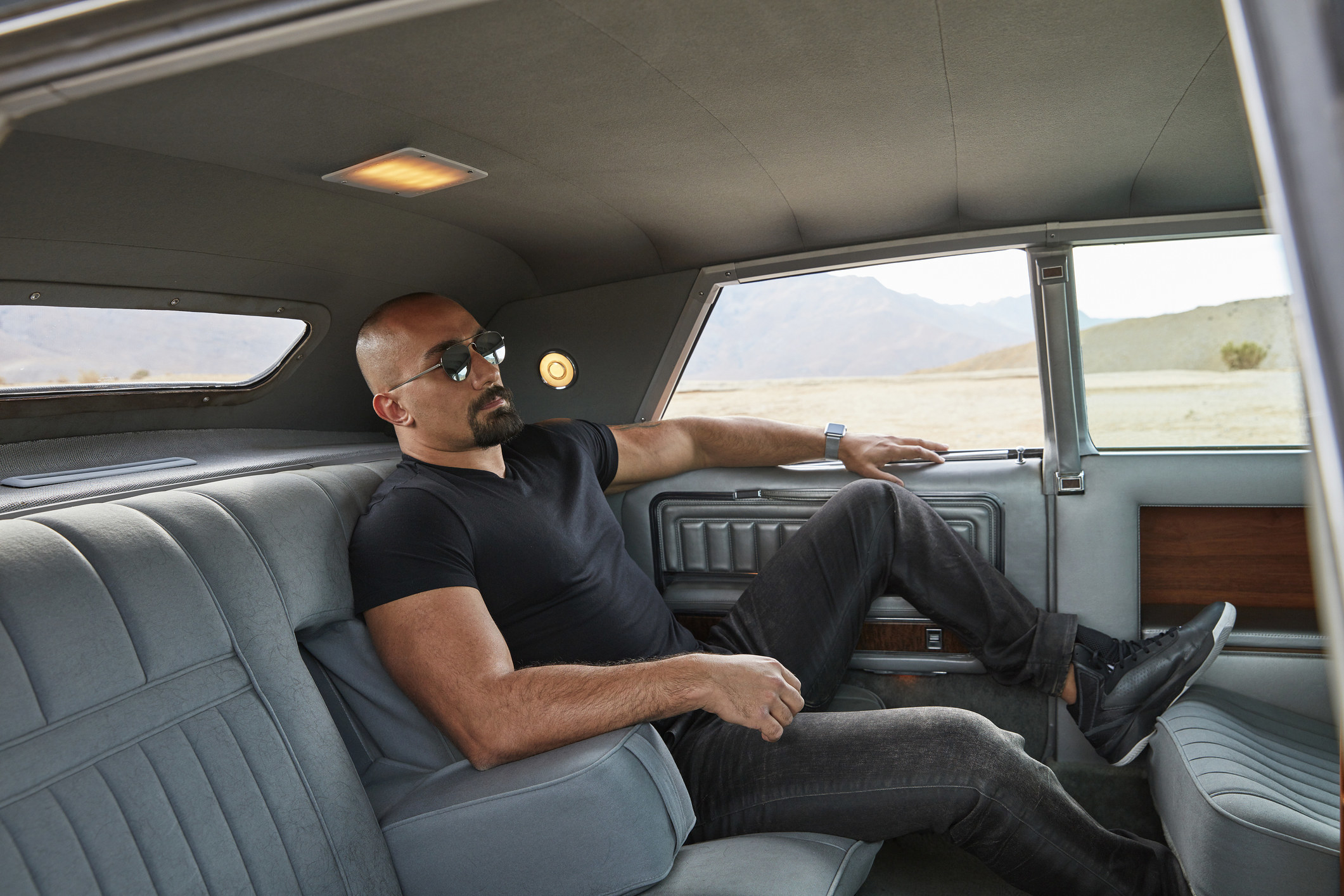 A man wearing sunglasses and lounging in the back of a spacious and expensive car