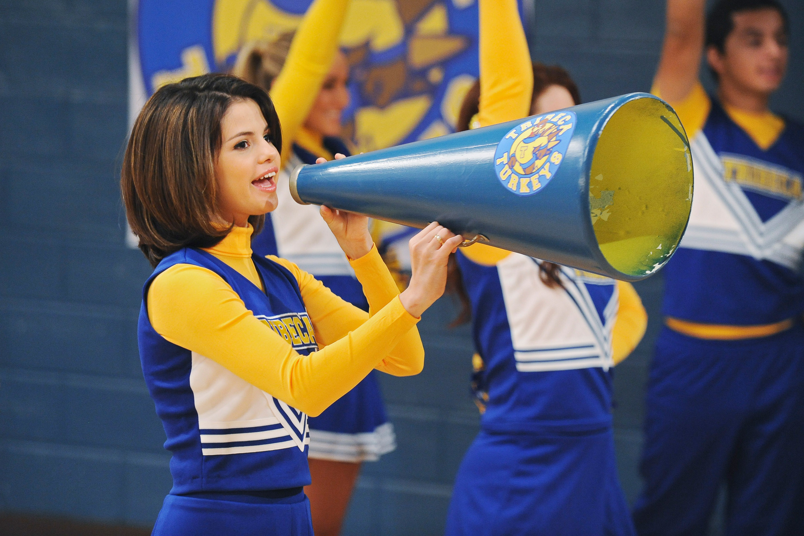 Selena Gomez in a cheerleading outfit shouts into a megaphone
