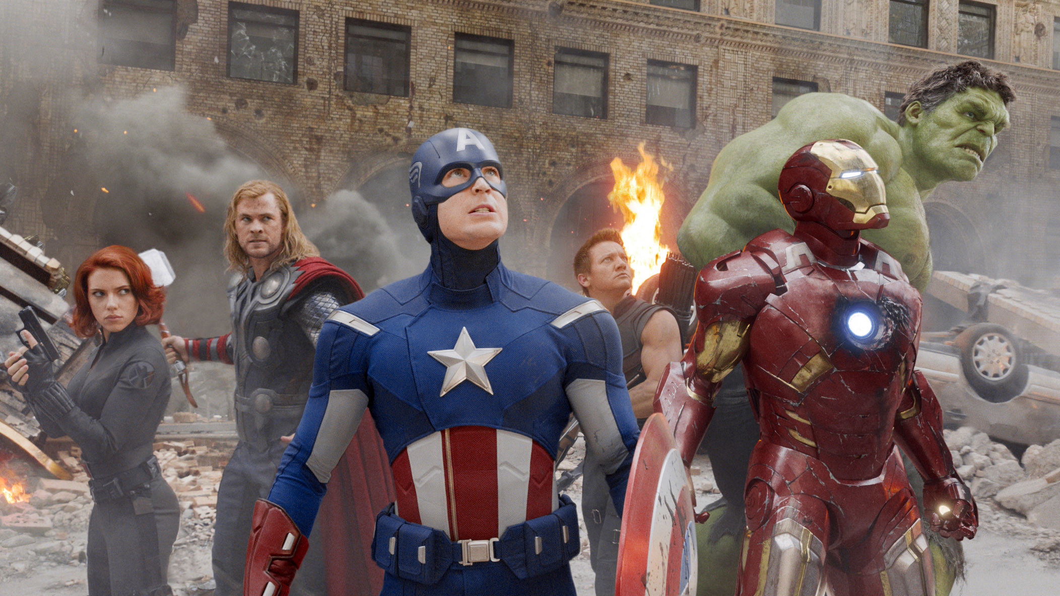 Black Widow standing with Thor, Captain America, Hawkeye, Iron Man, and the Hulk during a battle scene
