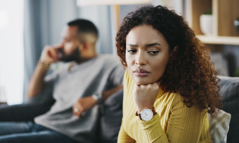 Woman looking sad while her boyfriend sits behind her on the couch
