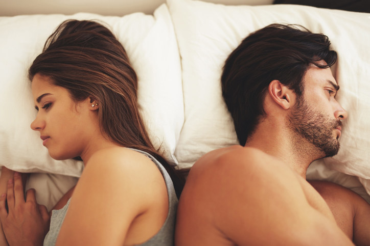 Couple facing away from each other in bed