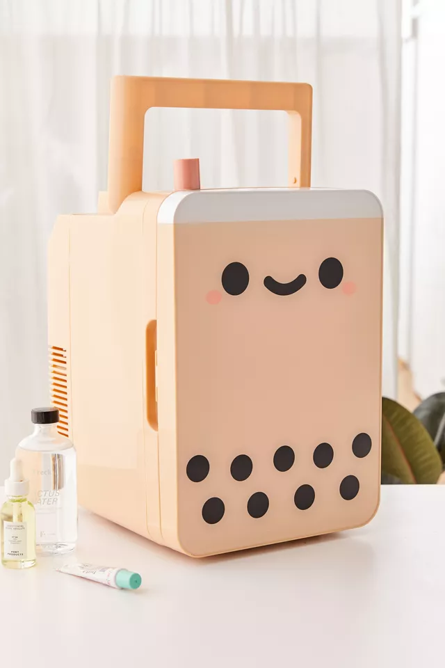 A tiny fridge on a table with beauty products beside it