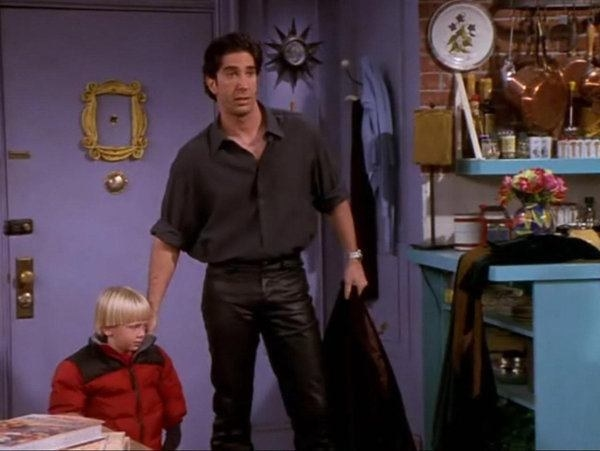 Ross wears leather pants and a matching button up shirt as he ushers his young son into Monica's apartment