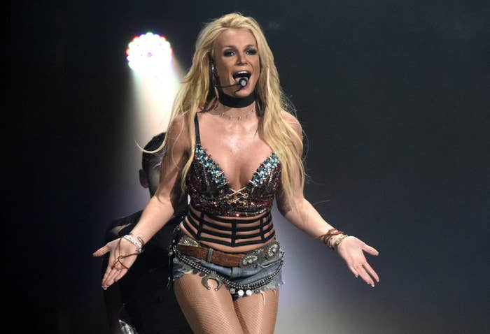Britney singing with a headset mic in jeans shorts and a bra-type top with her hands spread