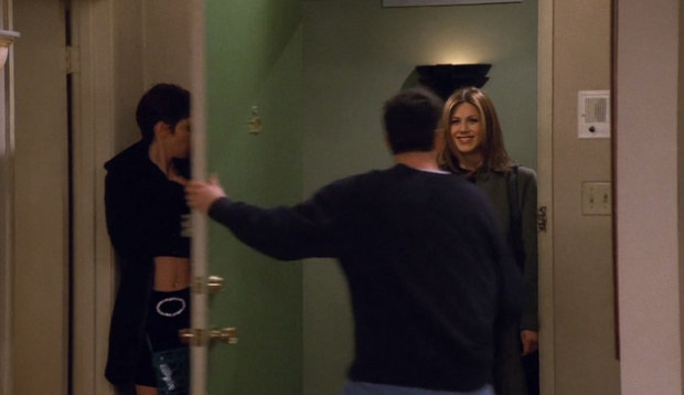 Ross holds his apartment door open for Rachel as Chloe hides behind it