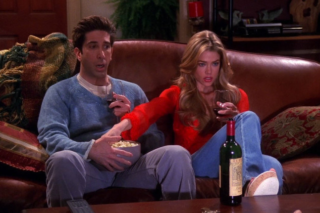 Ross' cousin reaches for the popcorn in his lap as Ross sits with his mouth open
