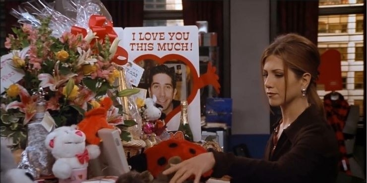 Rachel sits at her work desk which is overflowing with flower bouquets and a card with Ross' face on it