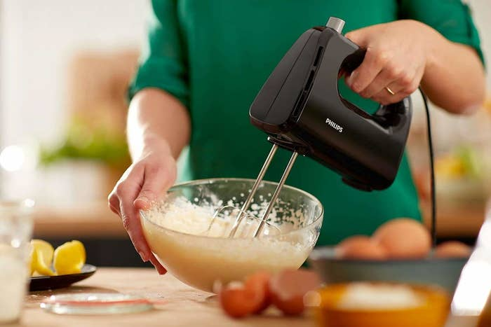 A person blending batter in a bowl with the hand mixer