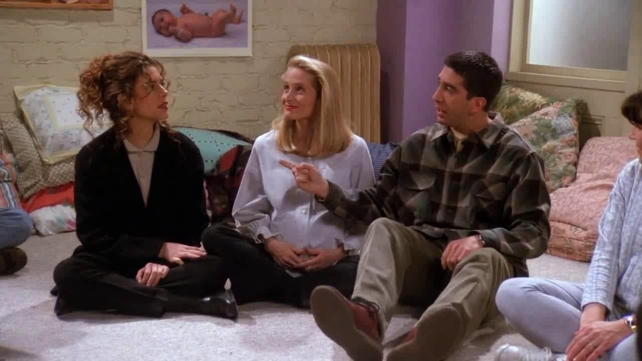 Ross points a finger at Susan, who glares at him while Carol sits between them smiling
