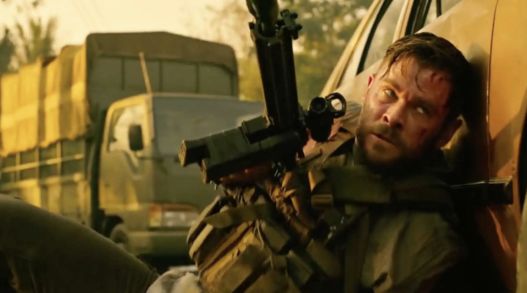 Chris Hemswork holding a gun in a scene set in Mexico with a yellow atmospheric filter