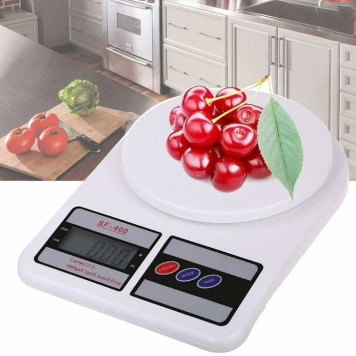 A white electronic weighing scale with a bunch of cherries kept on it