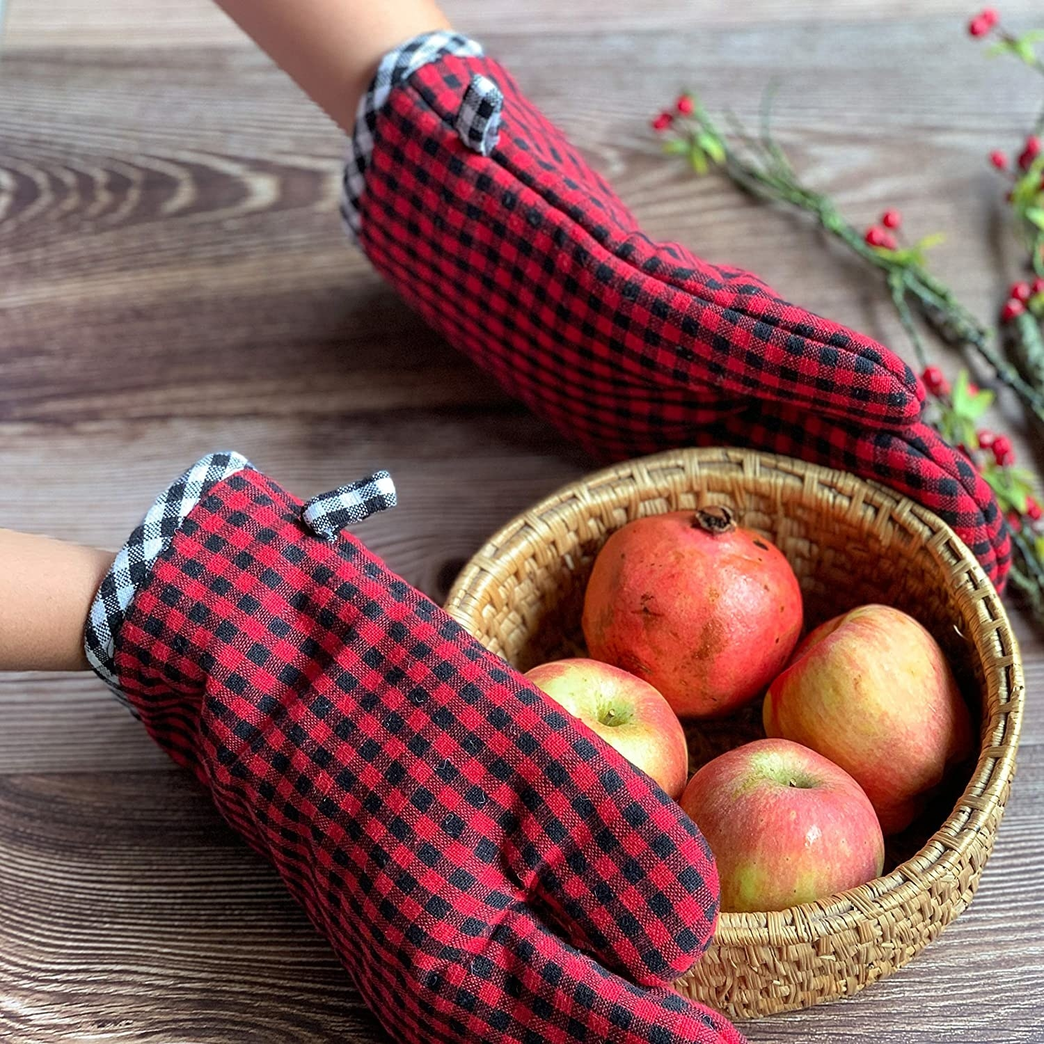 A person wearing black and red checkered mittens while holding a fruit basket