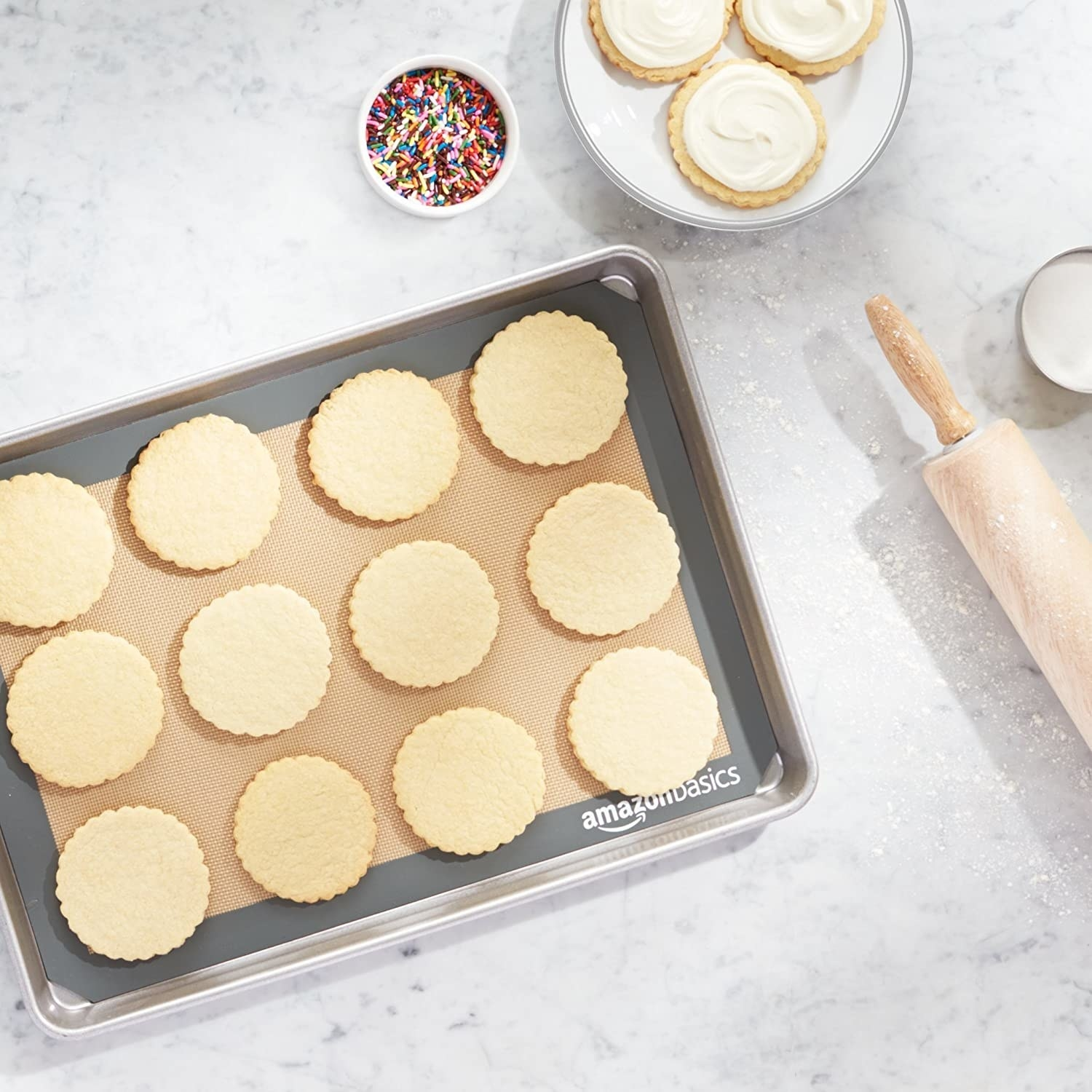 A silicone baking mat sheet lining a baking tray with cookies kept on it
