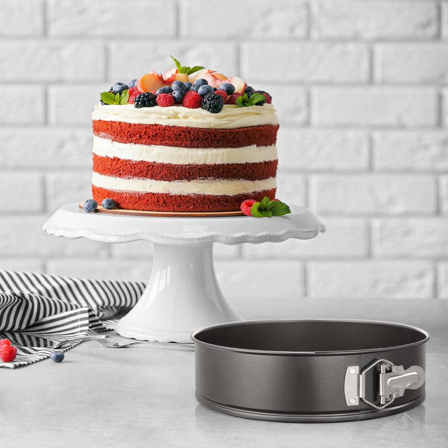 A teflon-coated cake mould sitting beside a frosted red velvet cake with fruits as decoration