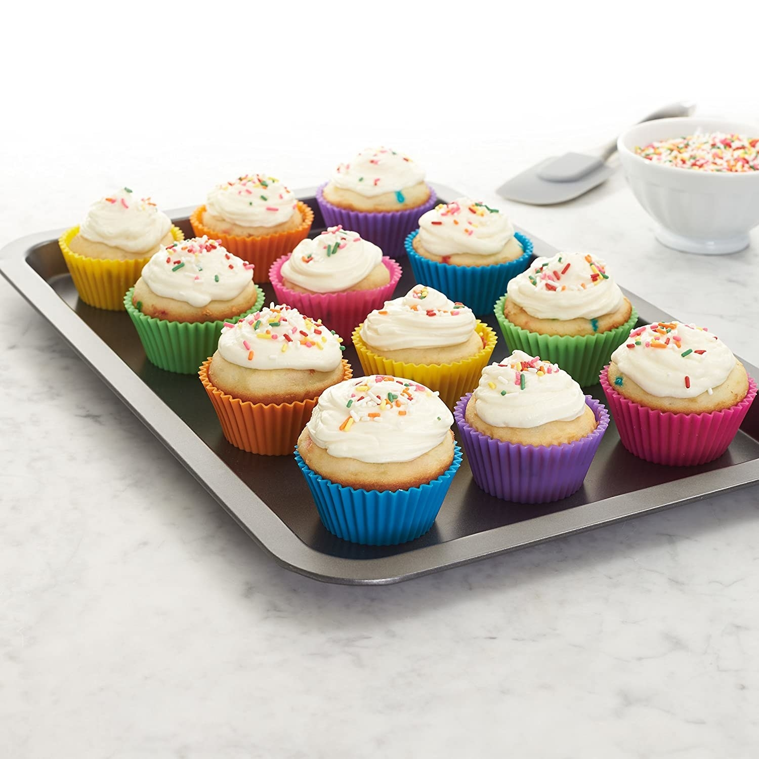 A tray of baked cupcakes in colourful silicone cupcake moulds