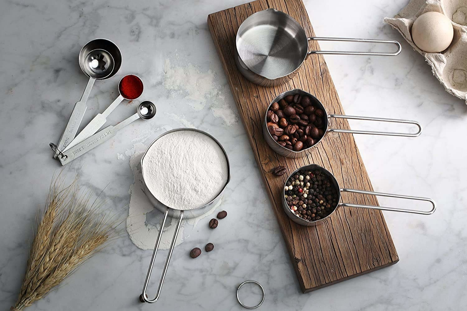 4 measuring cup and 4 measuring spoons filled with different ingredients like flour, coffee beans and spices