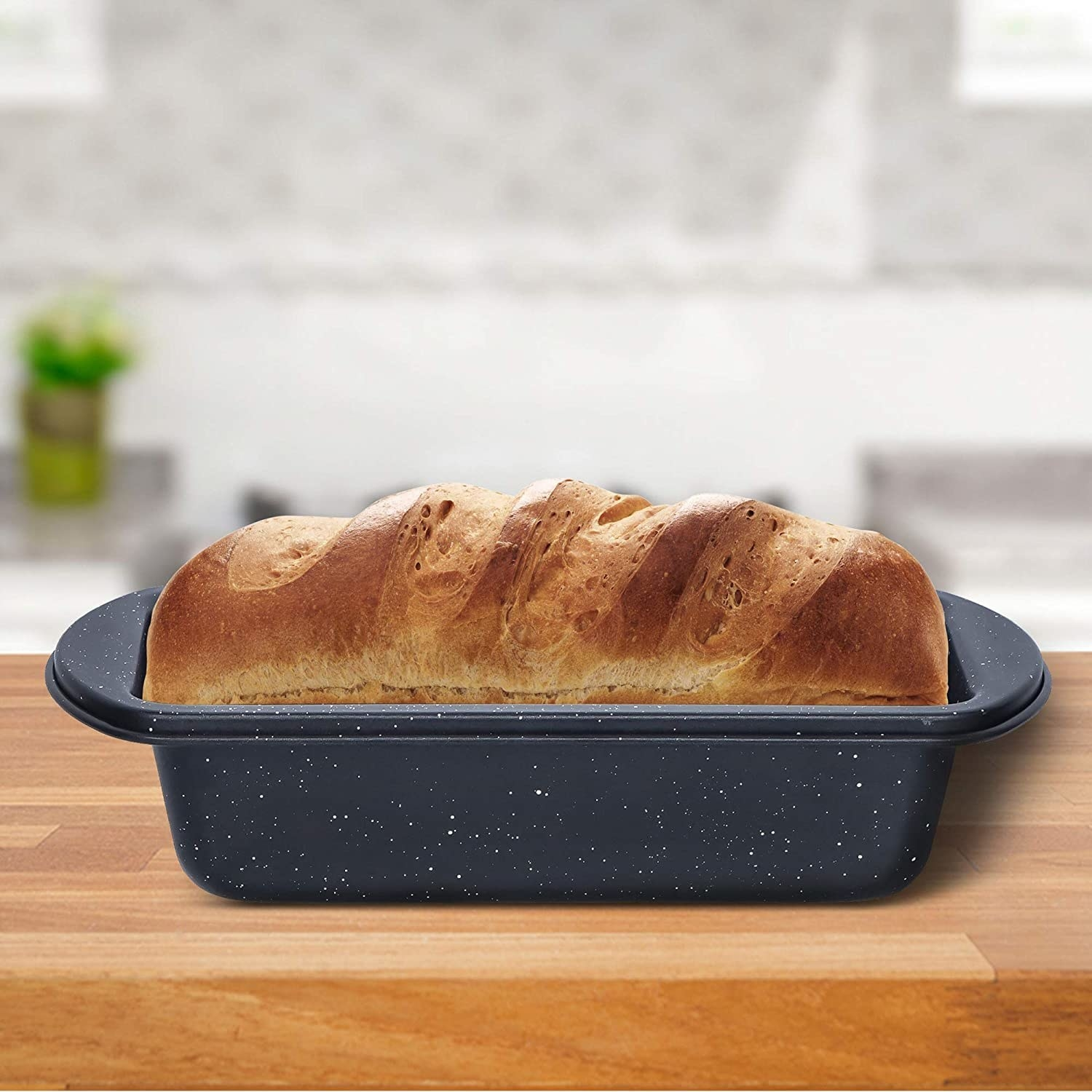 A baking loaf pan containing freshly baked bread