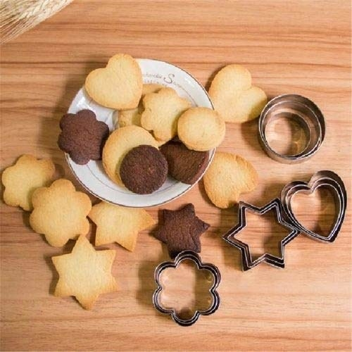A plate of cookies cut in star, heart and flower shapes kept beside cookie cutters with the same shapes