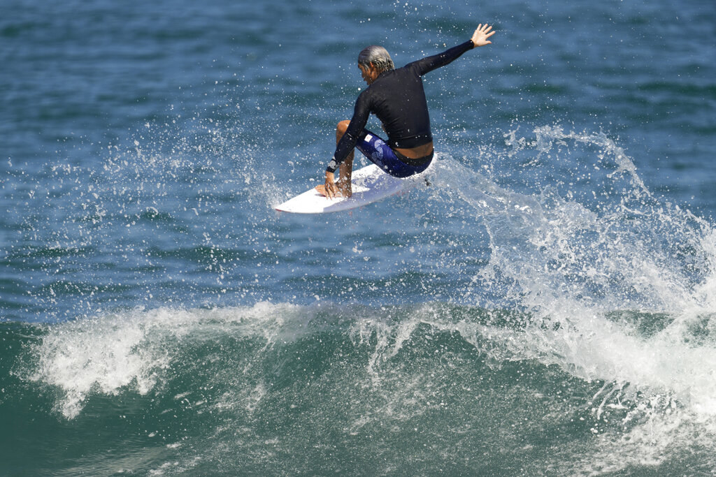 Kanoa crouched above a wave