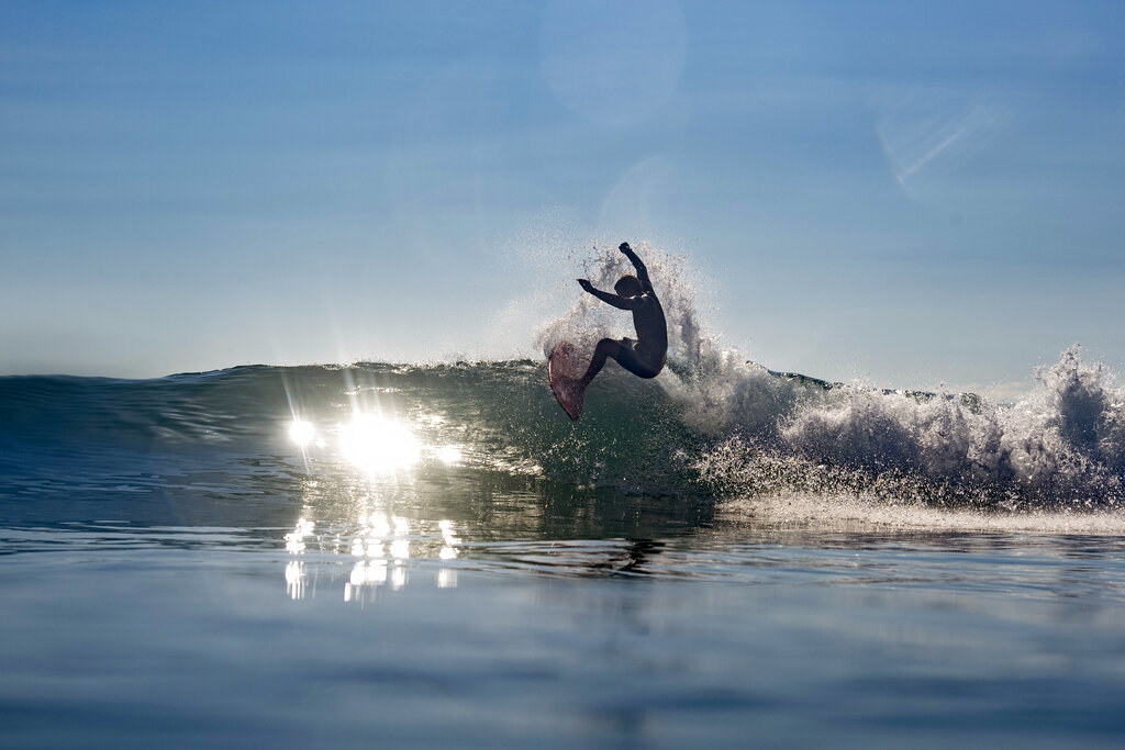 John John surfing, suspended in air, with sunlight hitting the water