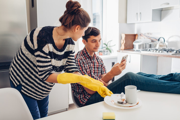 A person cleaning up with the person who made the mess looks at their phone