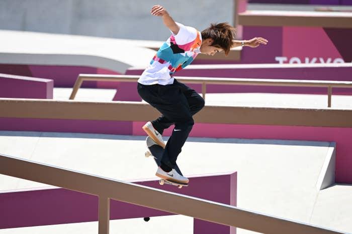 Yuto skateboarding down a handrail, arms raised, no helmet