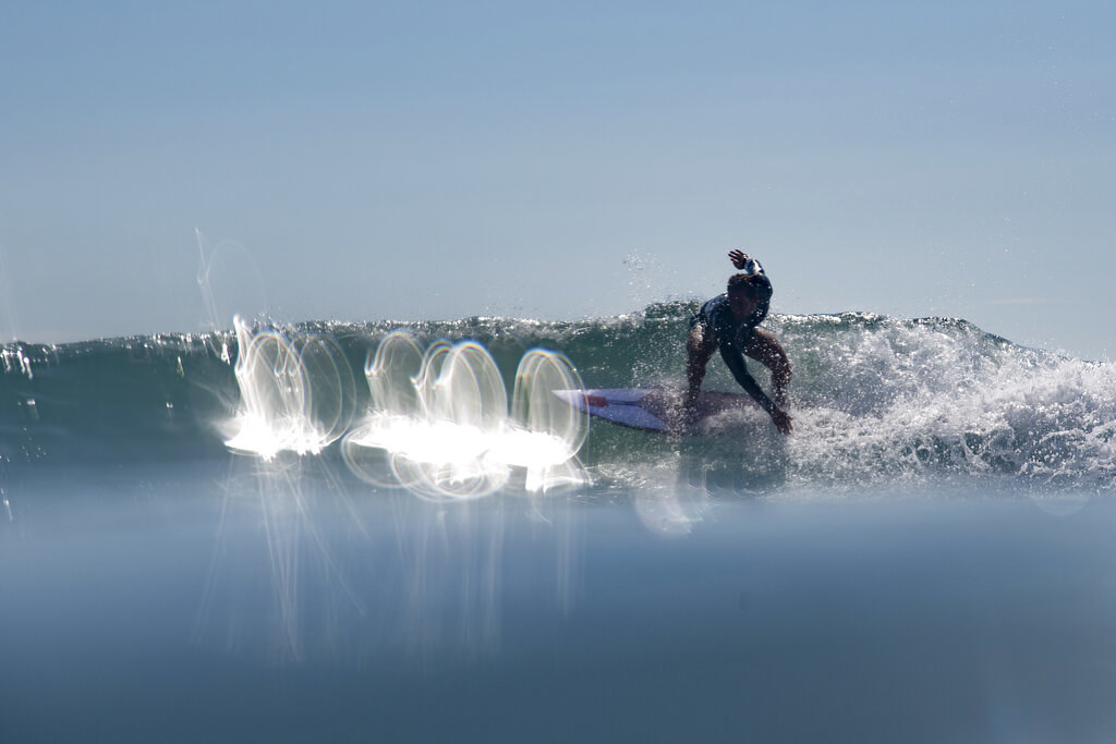 Manuel riding a wave in bright sunlight