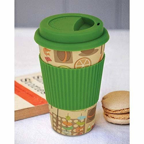 A beige mug with a green cap and silicone cover
