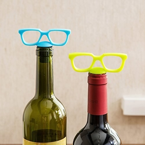 Wine stoppers that look like glasses on top of two bottles of wine