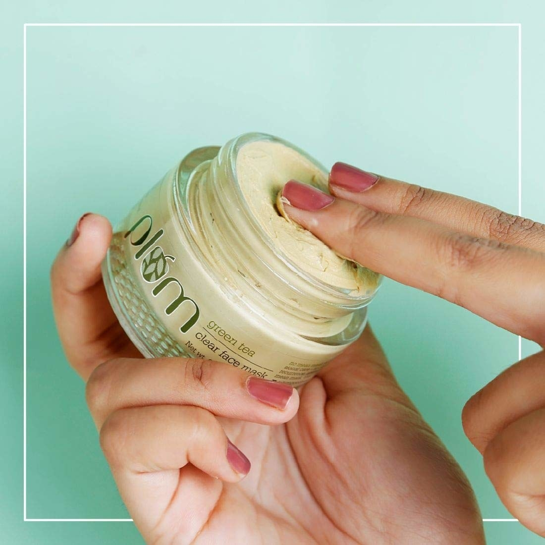 A hand holding the green tea clear face mask from Plum