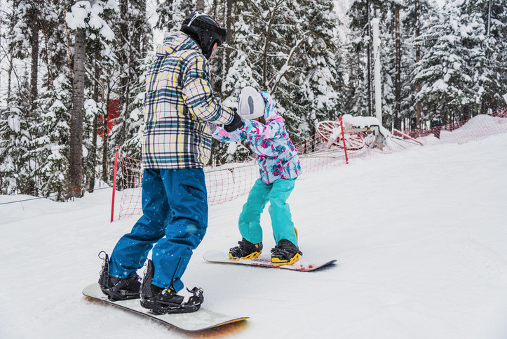 Snow board instructor with a young student