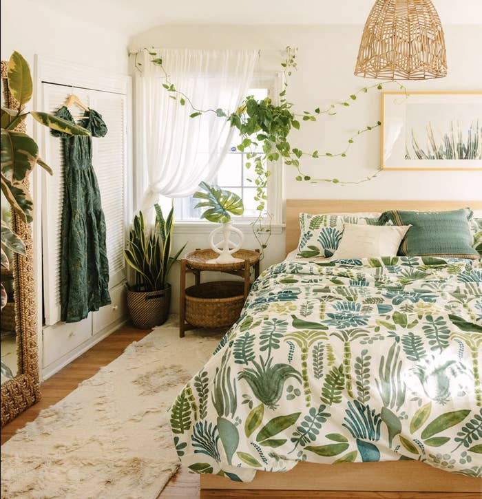 A beautiful bedroom with many green tones and plants and decor