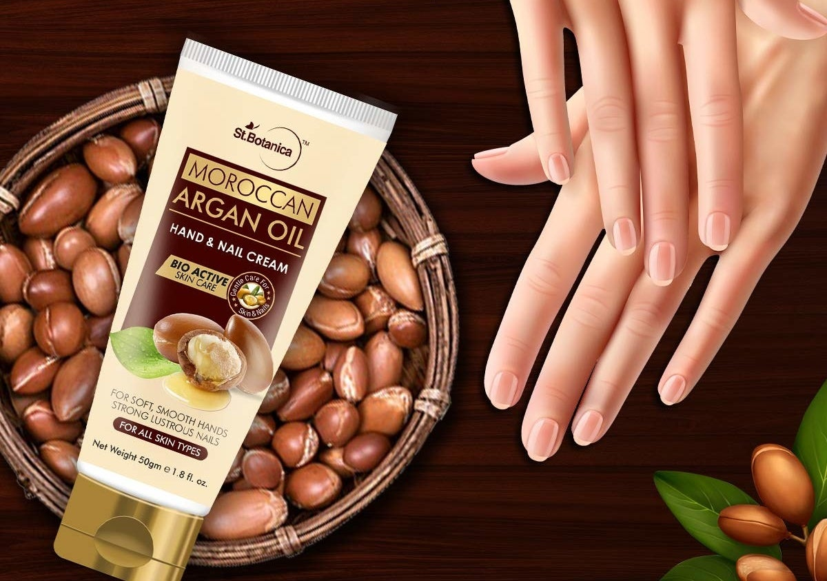 A tube of Moroccan argan oil kept on a bowl of Argan kernels and next to a pair of hand