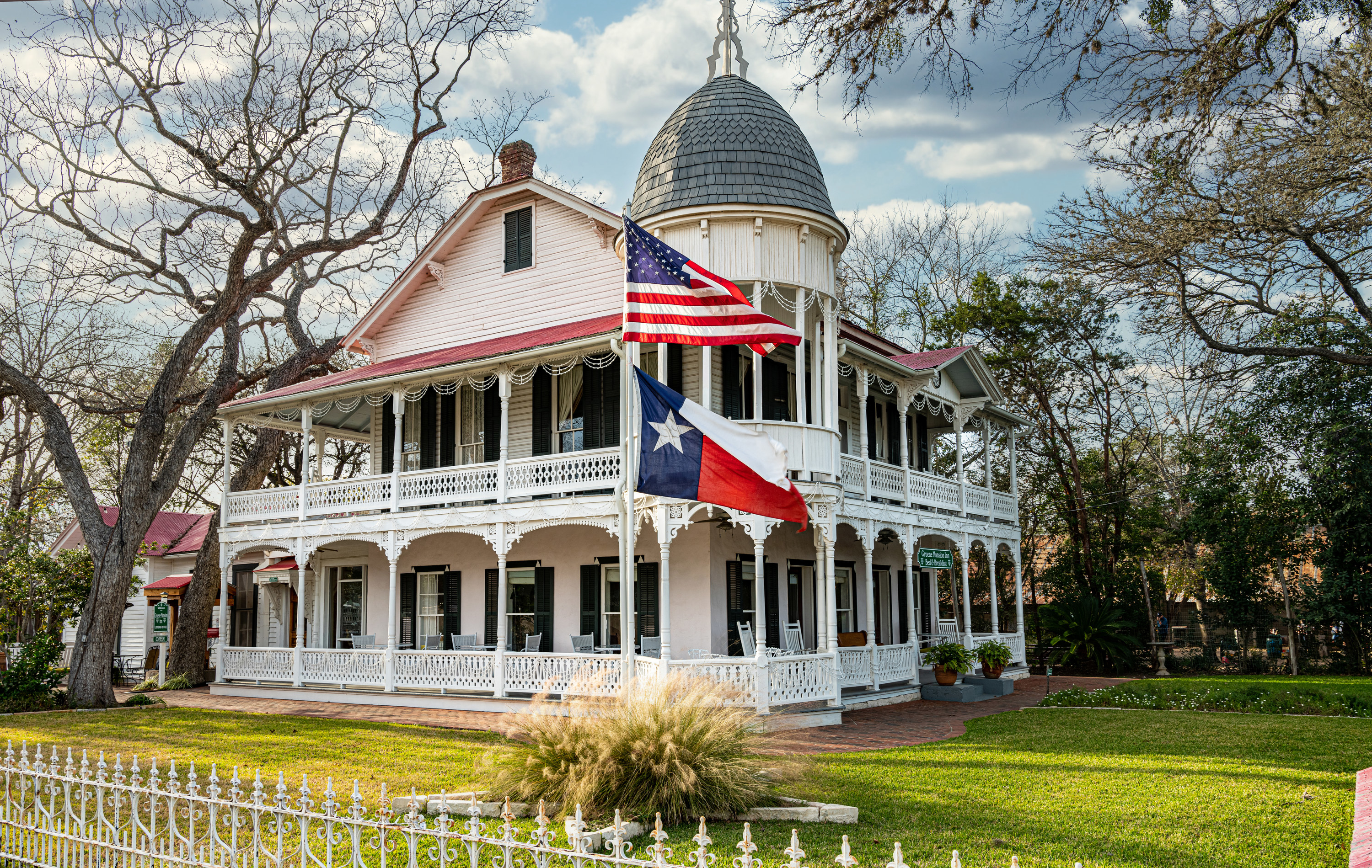 A grand white building in Gruene with the US and Texas flags flying in front