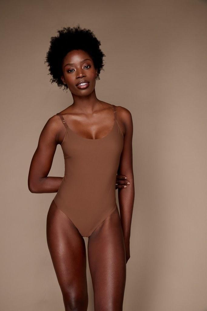 a dark skin model wearing a nude bodysuit in the color cinnamon