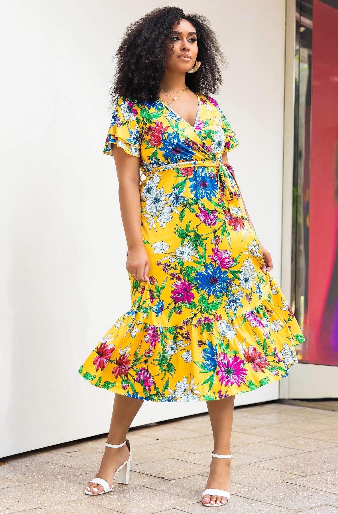 a plus size model wearing the birds of paradise midi skater dress with white heels
