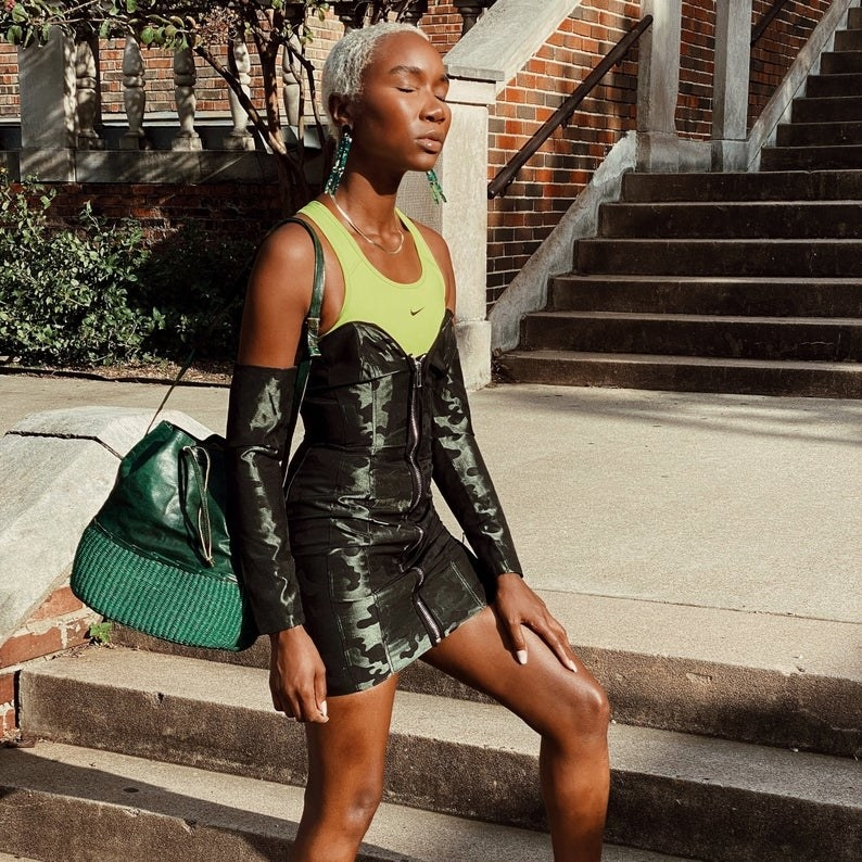 a model carries the green amma bucket bag over their shoulder