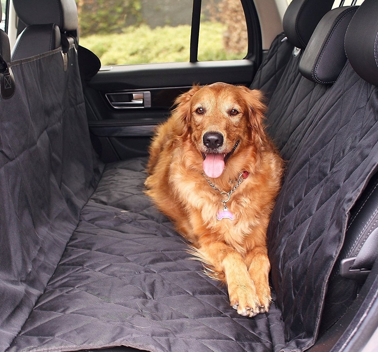 A Golden Retriever laying down in the backseat of a car with a car seat cover over the seats