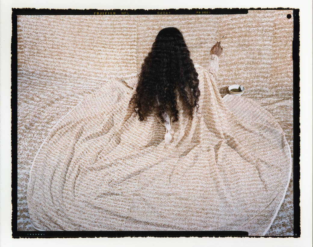 A long-haired woman in a robe paints a wall with the same pattern