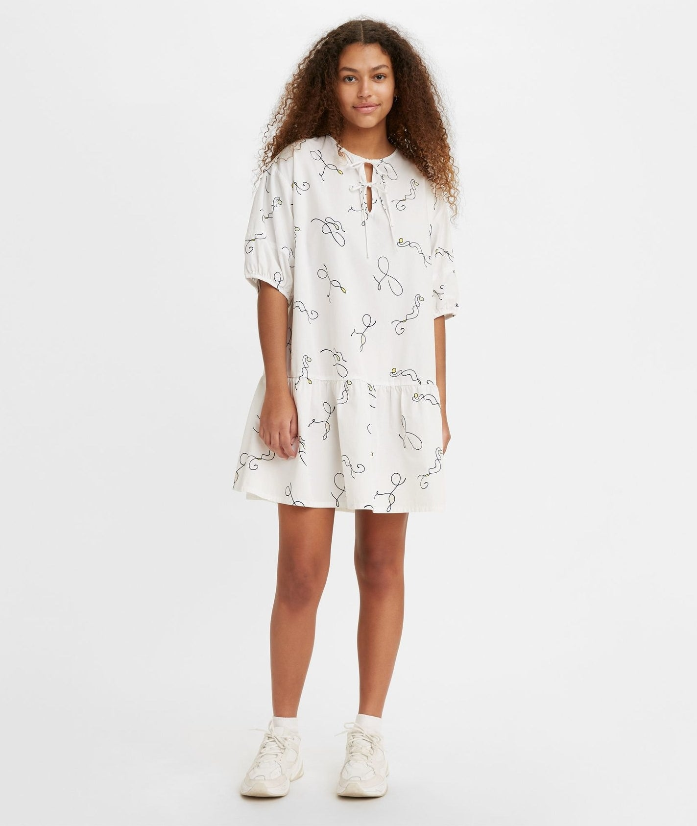 a model wearing the Isla puff sleeve dress with white sneakers