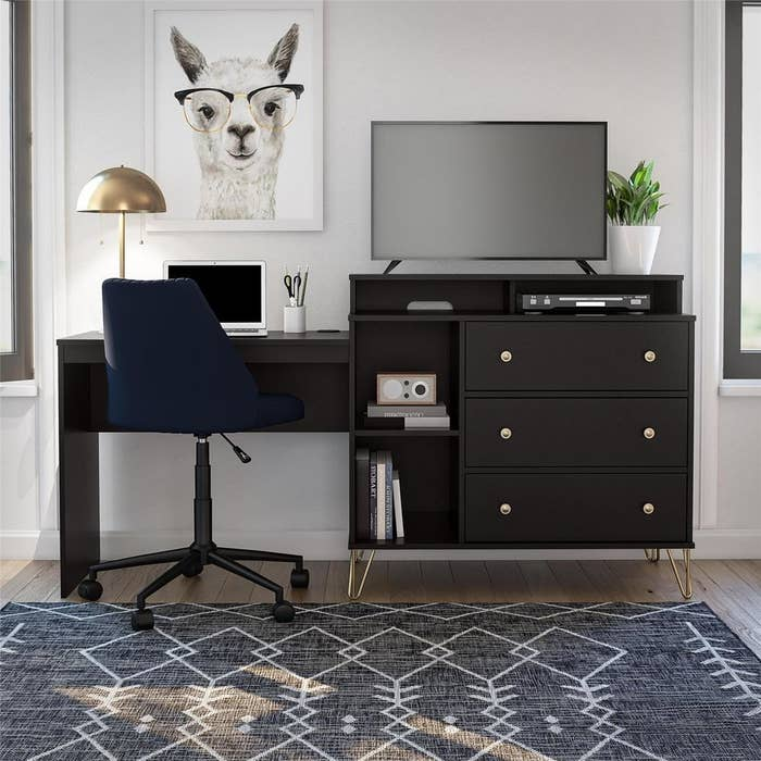 the desk which has two halves with one half actually being the desk with an office chair and laptop on the surface. the other side has two shelves for books, to smaller openings for cable boxes, and three drawers with a TV on the top