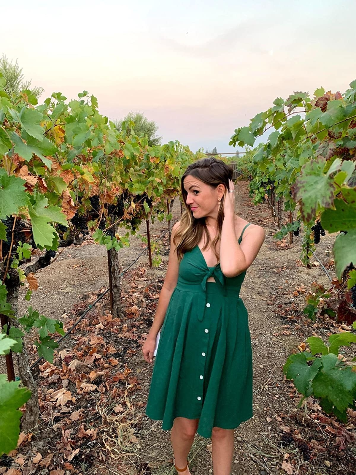 image of reviewer wearing the dark green tie front dress in a vineyard