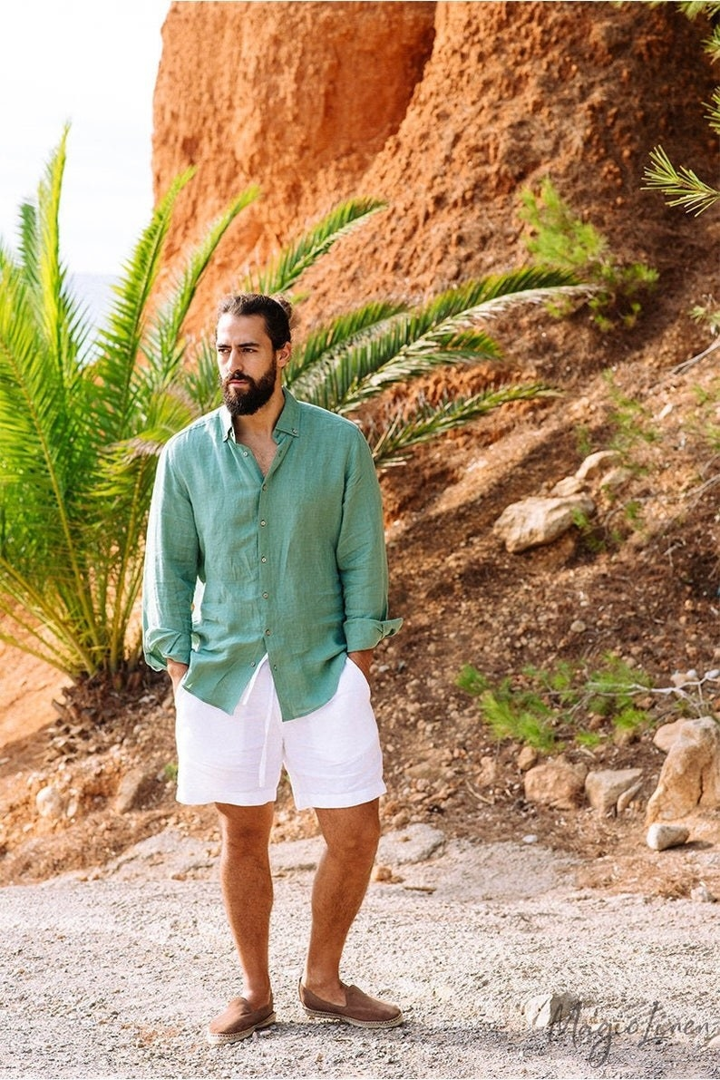 a model wearing the long sleeve green linen shirt next to a palm tree